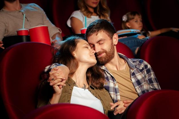 Amigos que sentam-se no filme do relógio do cinema que come a pipoca e a água bebendo. Foto Premium