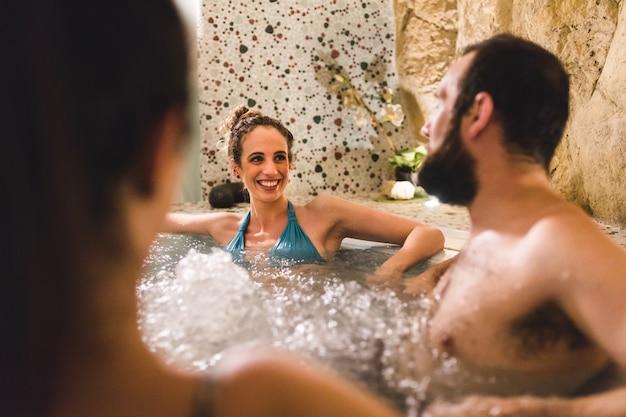 Amigos relaxantes e sorridentes na banheira jacuzzi no therme Foto Premium