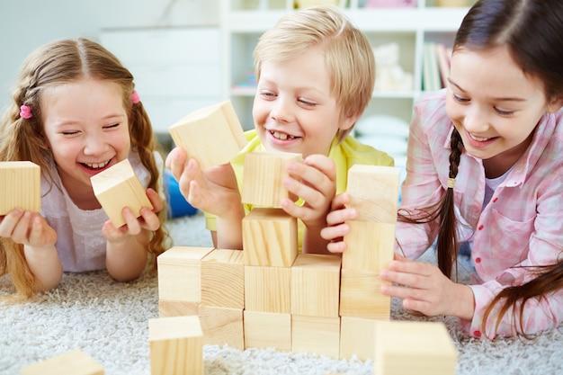 Amigos rindo com cubos de madeira Foto gratuita