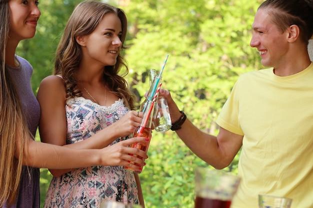 Amigos se divertindo e bebendo no acampamento Foto gratuita