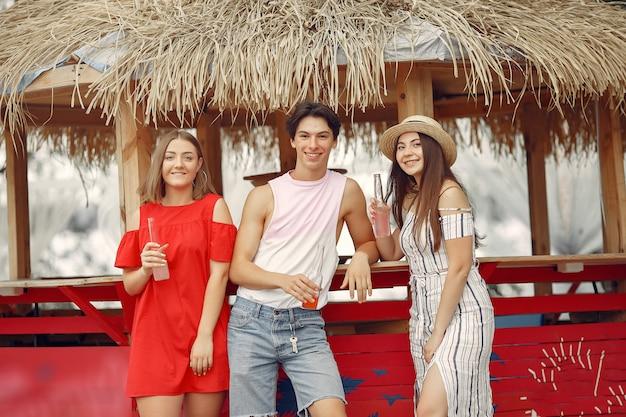 Amigos se divertindo na praia com bebidas Foto gratuita