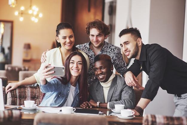 Amigos se divertindo no restaurante. três meninos e duas meninas fazendo selfie e rindo. no primeiro plano garoto segurando o telefone inteligente. todos usam roupas casuais Foto Premium