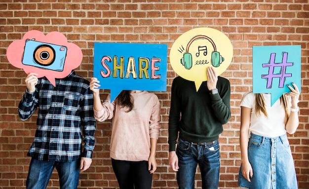 Amigos segurando balões de pensamento com ícones de conceito de mídia social Foto Premium