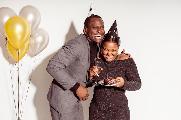 Amigos segurando bolo e rindo feliz festa de aniversário Foto gratuita