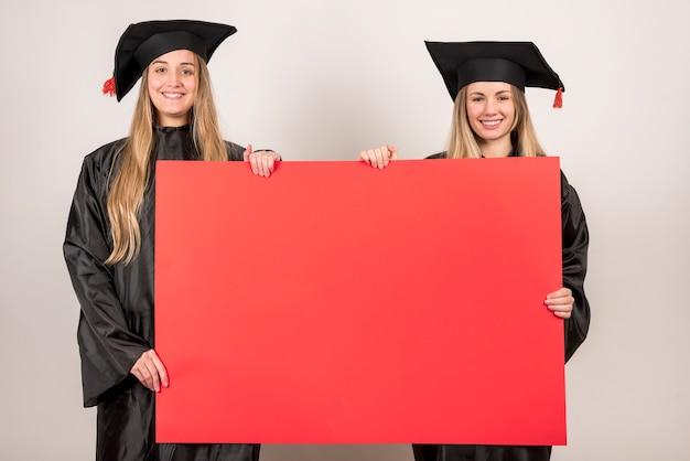 Amigos, segurando, vermelho, painél publicity, em, graduação Foto gratuita