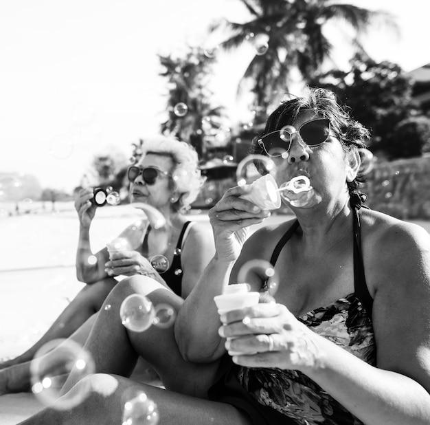 Amigos sênior, soprando, bolha, e, esfriando, praia Foto gratuita