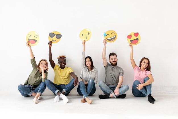 Amigos, sentada no chão e segurando emoji Foto gratuita