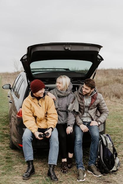 Amigos sentado atrás do carro Foto gratuita