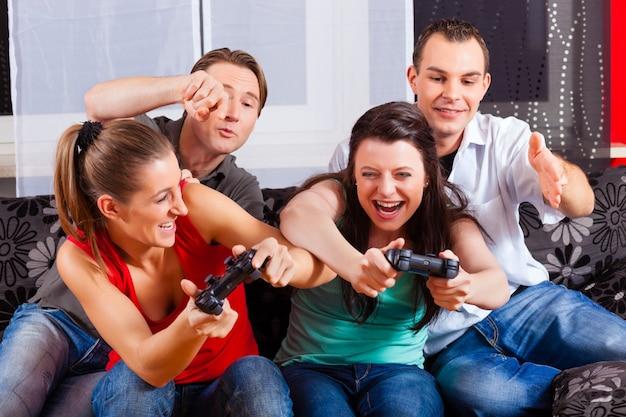 Amigos, sentado na frente da caixa do console de jogos Foto Premium
