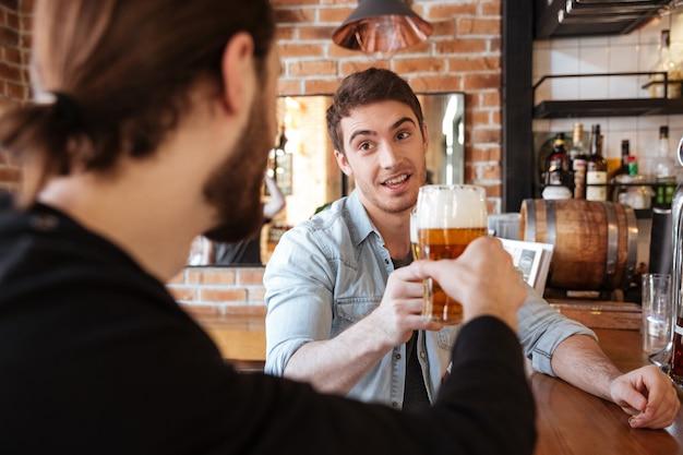 Amigos sentado no bar e bebendo Foto gratuita