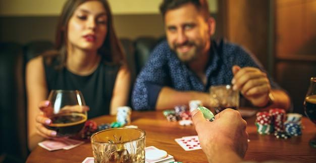 Amigos sentados à mesa de madeira. amigos se divertindo enquanto jogam o jogo de tabuleiro. Foto gratuita