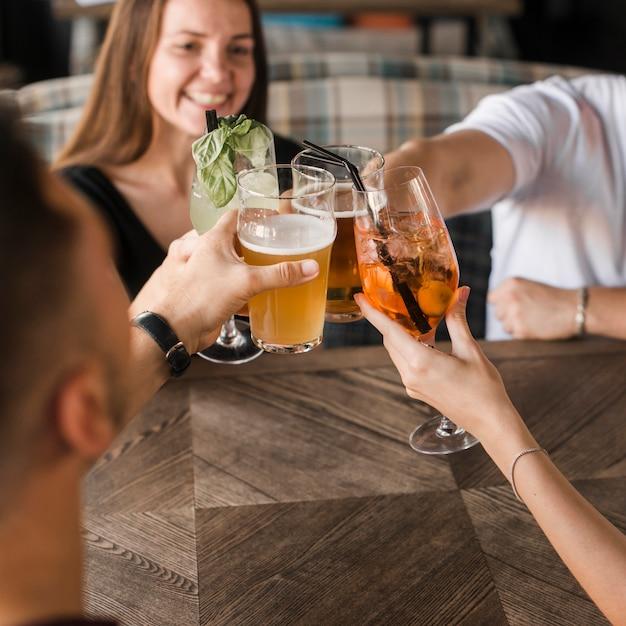 Amigos sentados juntos no bar brindando conjunto de bebidas Foto gratuita
