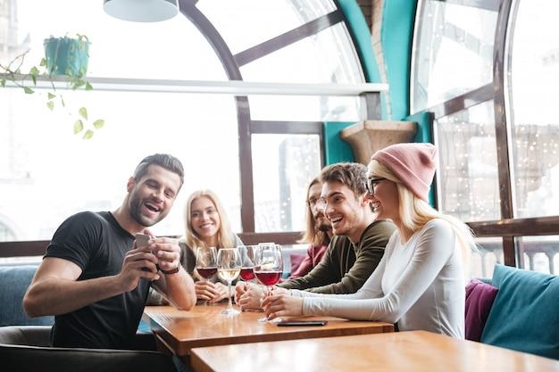 Amigos sorridentes no café a beber álcool e fazer um selfie. Foto gratuita