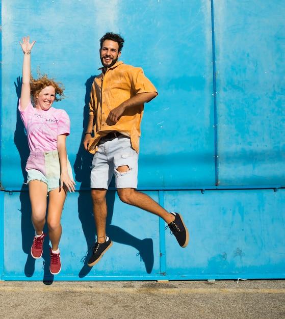Amigos sorridentes pulando com fundo azul Foto gratuita