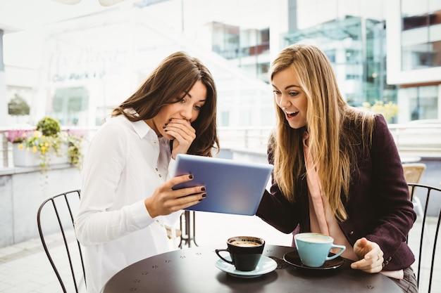 Amigos surpresos, olhando para tablet no café Foto Premium