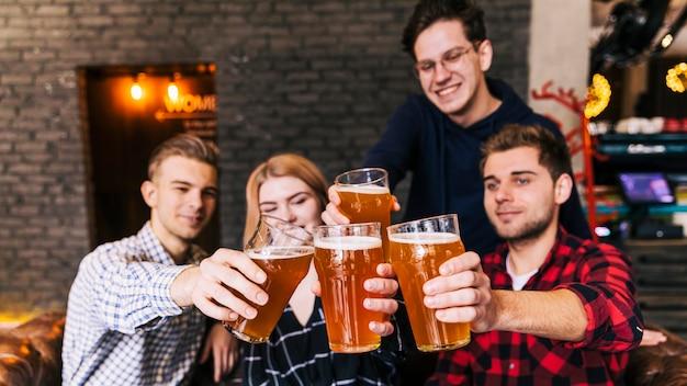 Amigos tilintar de copos com cerveja no pub Foto gratuita