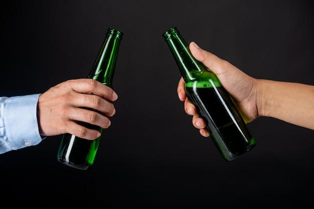 Amigos, tilintar garrafas de cerveja Foto gratuita