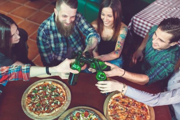 Amigos, tomar uma bebida em um bar, eles estão sentados em uma mesa de madeira com cervejas e pizza. Foto Premium