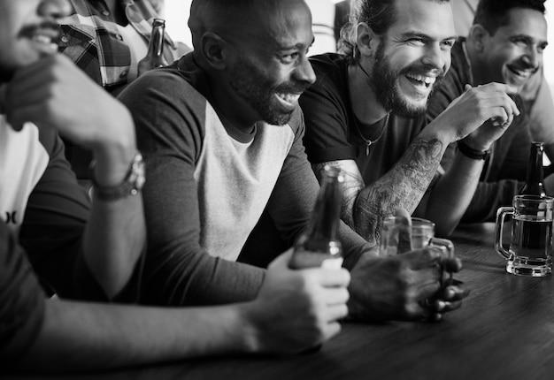 Amigos torcendo esporte no bar juntos Foto gratuita