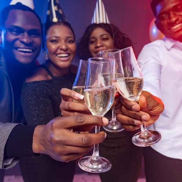 Amigos usando chapéus de festa e brindando com champanhe Foto gratuita
