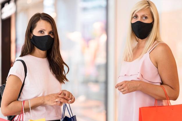 Amigos usando máscaras de tecido em shopping Foto gratuita