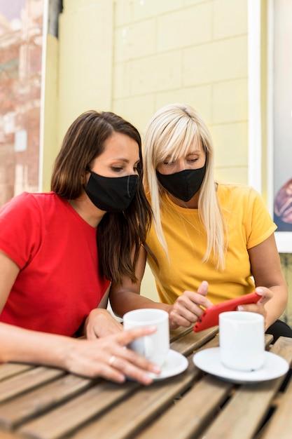 Amigos usando máscaras e tomando um café juntos Foto gratuita