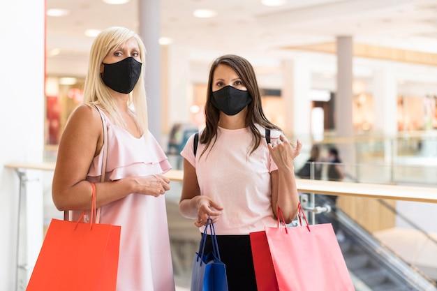 Amigos usando máscaras em shopping e segurando sacolas de compras Foto Premium