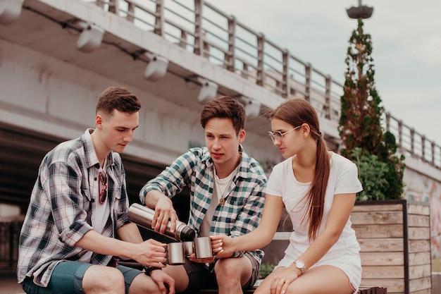 Amigos-viajantes usando garrafa térmica durante uma caminhada de verão pela cidade Foto Premium