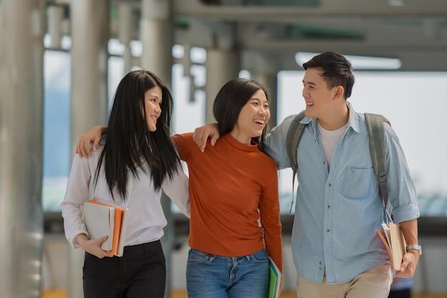 Amizade no campus, estudantes universitários com livros passam tempo juntos. Foto Premium