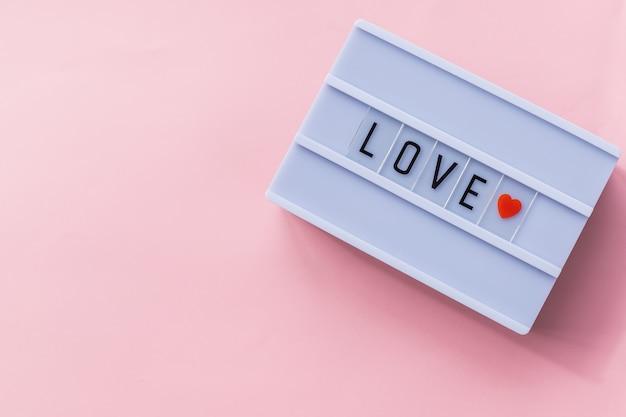 Amo texto em uma caixa de luz. caixa isolada sobre fundo rosa. um sinal com uma mensagem. bandeira do dia dos namorados. fundo de férias, cartão festivo. copie o espaço. pode ser usado para o dia dos namorados de celebrações. Foto Premium