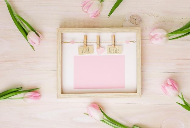 Amor e beijos inscrição no quadro com tulipas Foto gratuita