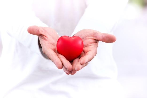Amor e conceito saudável; coração vermelho na mão, cuide-se com amor. Foto Premium