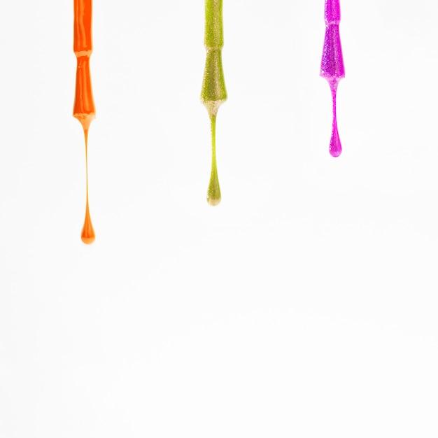 Amostras de várias cores de esmalte sobre as escovas sobre fundo branco Foto gratuita