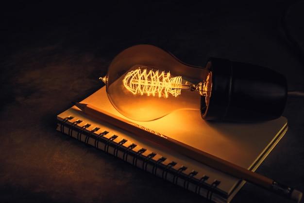 Ampola em um caderno com lápis, inspiração e conceito do fundo da educação. Foto Premium