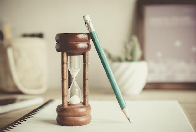 Ampulheta com lápis no notebook, conceito de passagem de tempo Foto Premium