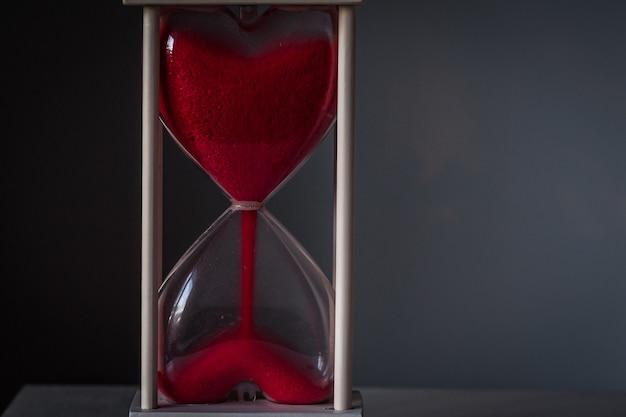 Ampulheta como conceito de amor para dia dos namorados no fundo cinzento escuro. Foto Premium