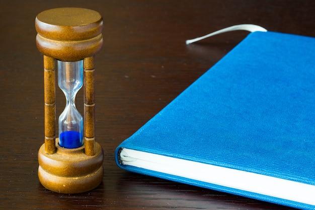 Ampulheta ou areia de vidro sobre uma mesa Foto Premium