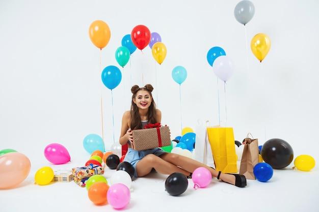 Amuzed menina adolescente depois da festa de aniversário. segurando uma enorme caixa de presente Foto gratuita