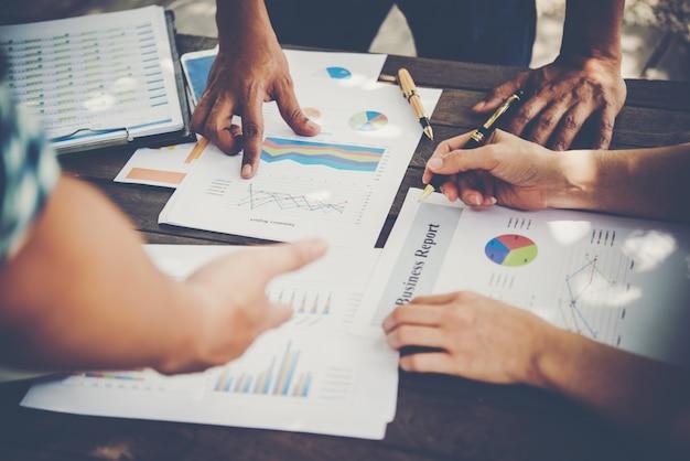 Análise do grupo de empresas com gráfico de relatório de marketing, jovens especialistas estão discutindo idéias de negócios para o novo projeto de inicialização digital. Foto gratuita