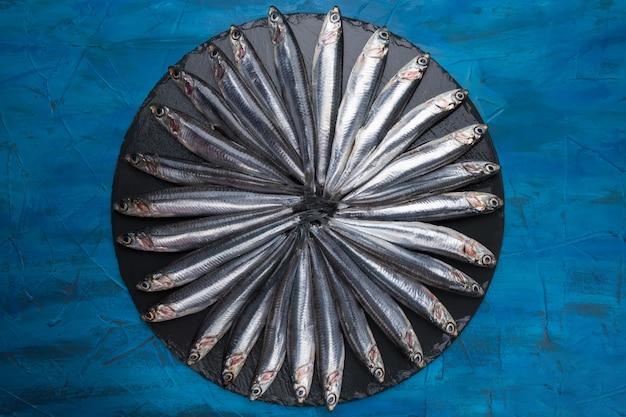 Anchovas na forma de um círculo em uma pedra preta. frutos do mar. peixe pequeno mar Foto Premium