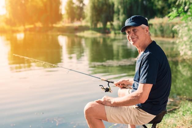 Ancião com gray hair fishing no rio no verão. Foto Premium