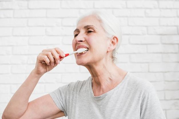 Ancião, mulher, lavando, dela, dentes Foto gratuita