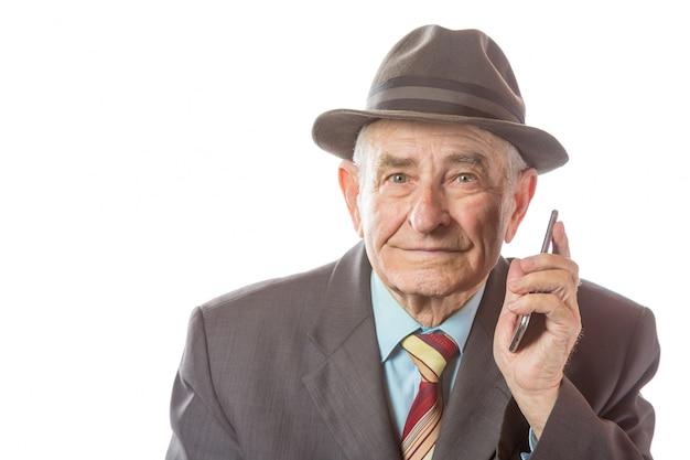 Ancião sênior idoso com um chapéu retro que fala no telefone móvel isolado no fundo branco. Foto Premium
