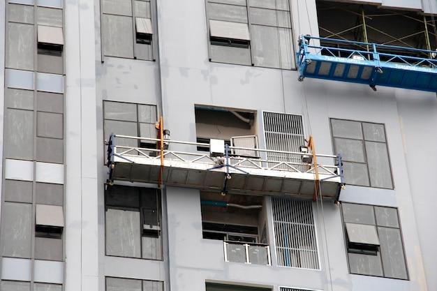 Andaime para limpar a janela no edifício alto. Foto Premium