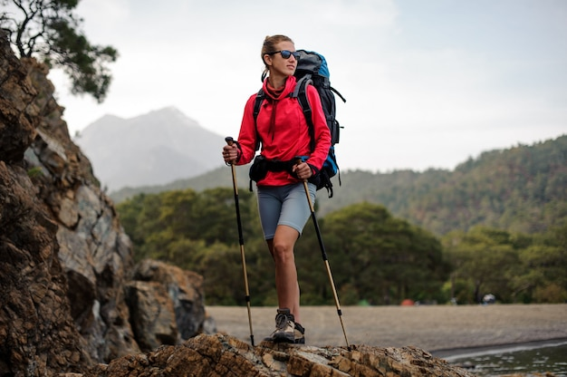 Andarilho feminino posando em cima da pedra Foto Premium