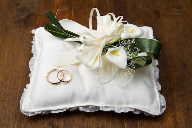 Anéis de casamento com buquê de calla no travesseiro nupcial Foto Premium