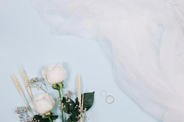 Anéis de casamento com flores e véu de noiva Foto gratuita