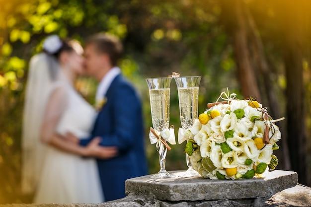 Anéis de casamento com rosas e taças de champanhe e um beijo do noivo e da noiva Foto Premium