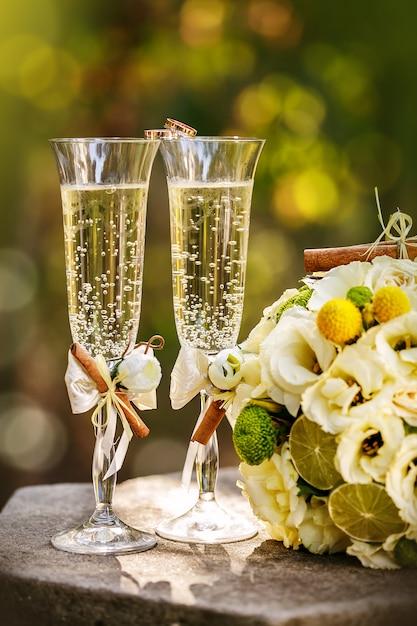 Anéis de casamento com rosas e taças de champanhe Foto Premium
