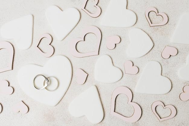 Anéis de casamento de diamante em forma de coração branco e rosa sobre o pano de fundo concreto Foto gratuita